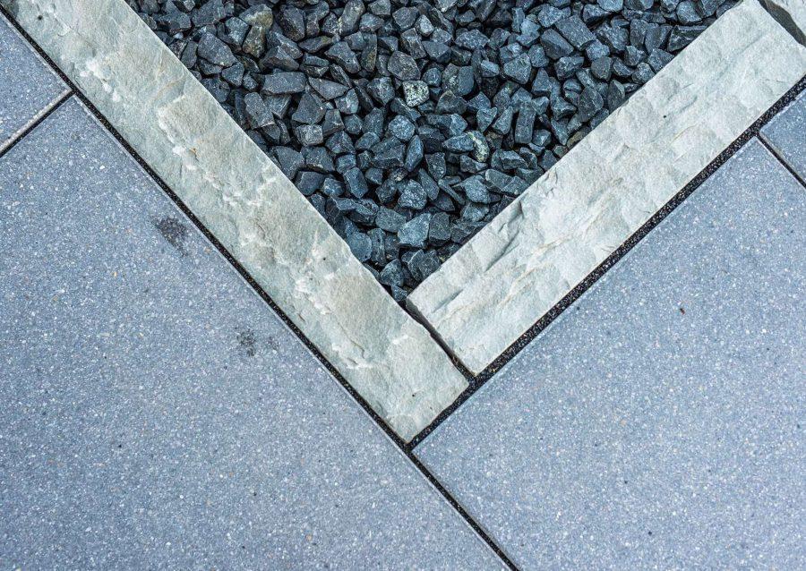 Terrasse durch Kantensteine aus Sandstein erhöht, hebt sich von Rasen- und Beetflächen ab